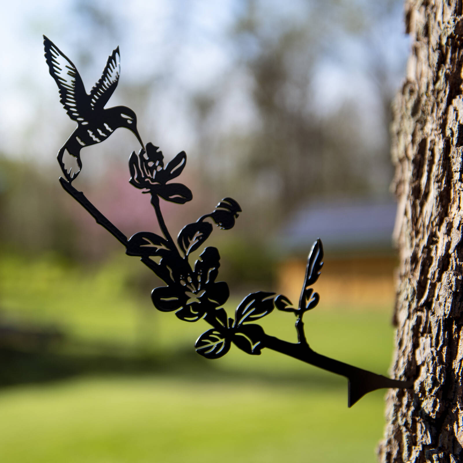 Decorative metal hummingbird attached to tree product photo by Robintek Photography